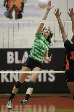 Trinity Catholic player Ali Palma spikes the ball around the outstreched arms of Stamford's Brianna Aias duing FCIAC volleyball action at Stamford High School. Stamford won the Thursday game in three straight matches. Photo: J. Gregory Raymond / Stamford Advocate Freelance;  © J. Gregory Raymond