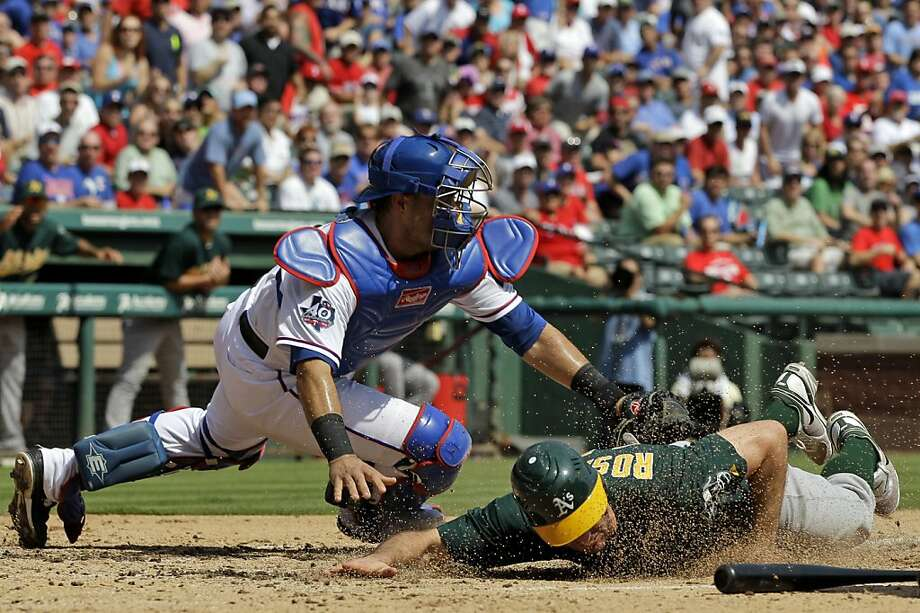 Oakland Athletics' Adam Rosales scores at under the attempted tag by Texas Rangers' Geovany Soto during the third inning of a baseball game Thursday, Sept. 27, 2012, in Arlington, Texas. Rosales reached home safely on a Jonny Gomes double. (AP Photo/Tony Gutierrez) Photo: Tony Gutierrez, Associated Press