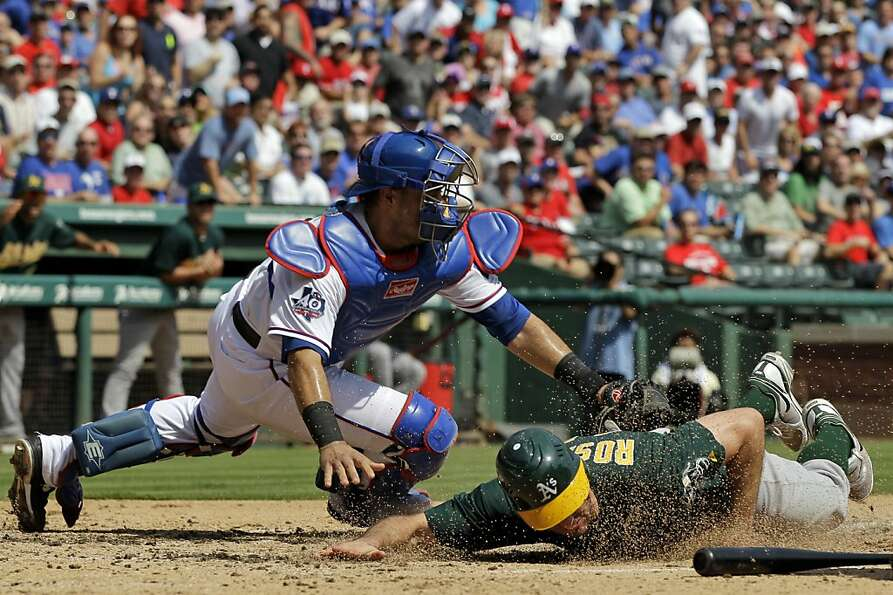Oakland Athletics' Adam Rosales scores at under the attempted tag by Texas Rangers' Geovany Soto dur