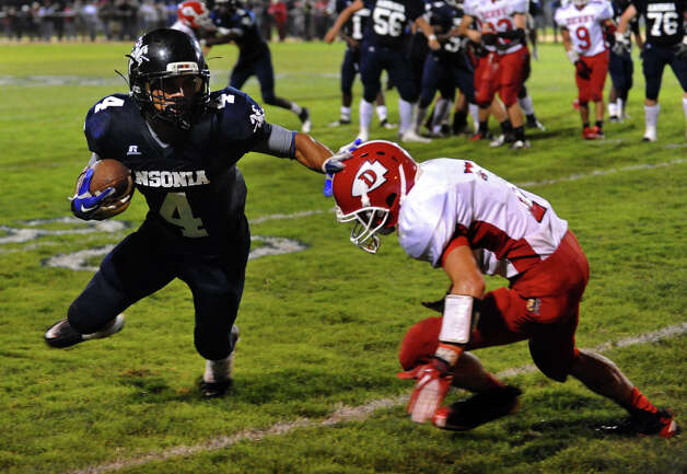 Ansonia's #4 Andrew Matos, left, looks to dodge a tackle by Derby's #7 Dillon McMahon, during football action in Ansonia, Conn. on Thursday September 27, 2012. Photo: Christian Abraham / Connecticut Post