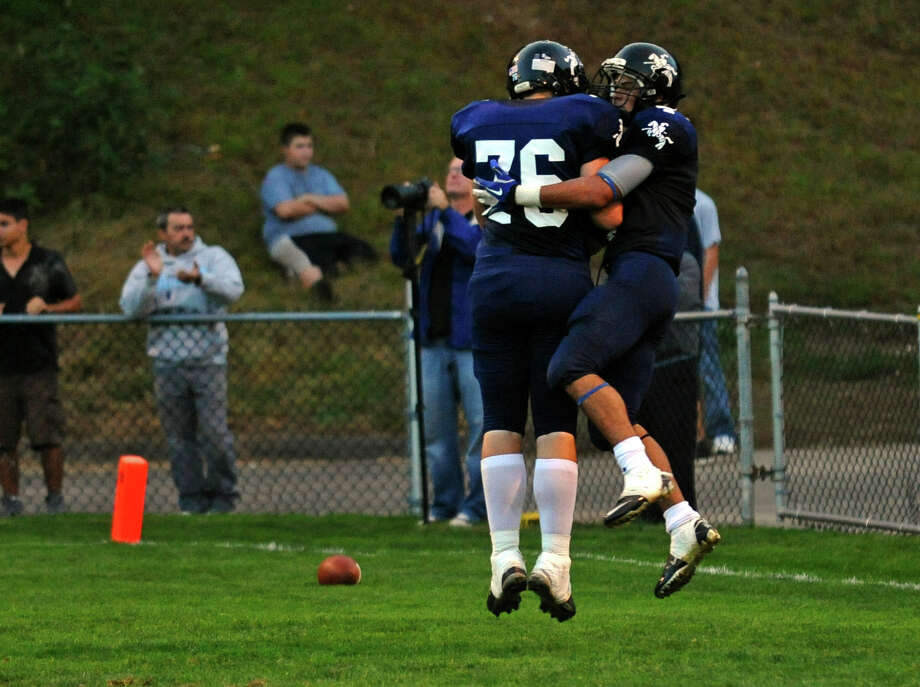 Ansonia's #4 Andrew Matos, right, leaps in the air to celebrate his touchdown with teammate Corey Dzienkiewicz, during football action in Ansonia, Conn. on Thursday September 27, 2012. Photo: Christian Abraham / Connecticut Post