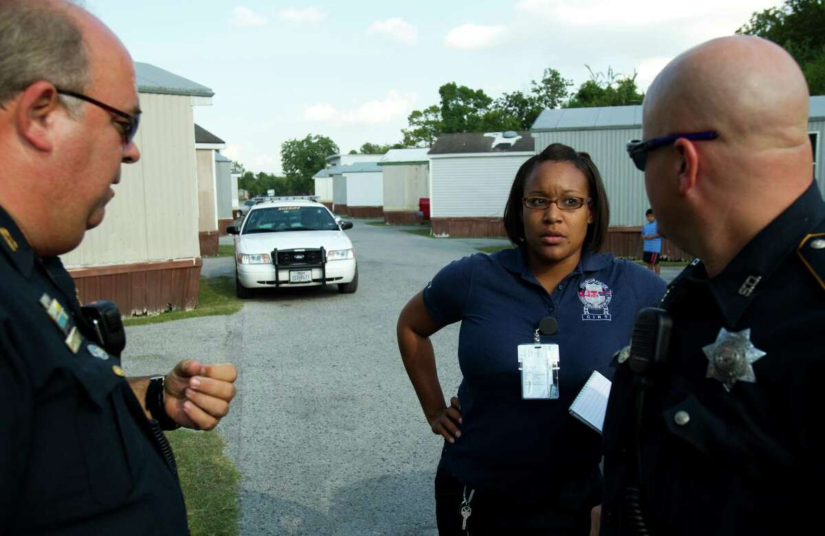 Lt. Robert Henry, left, therapist Kendra Lee and Deputy Don Hess discuss a crisis situation Wednesday in Houston.
