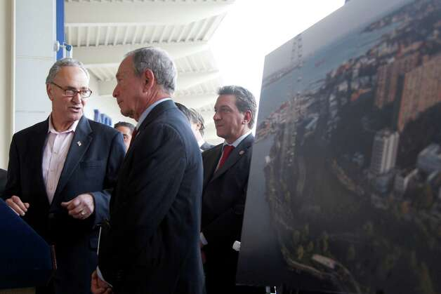 "Sen. Charles Schumer, D-N.Y., and New York City Mayor Michael Bloomberg stand next to an artist rendering of a proposed Ferris wheel during a news conference on the Staten Island borough of New York, Thursday, Sept. 27, 2012.  The proposed 625-foot Ferris wheel, billed as the world's largest, planned as part of a retail and hotel complex along the Staten Island waterfront in New York. The attraction, called the New York Wheel, will cost $230 million. Officials say the observation wheel will be higher than the Singapore Flyer, the London Eye, and a ""High Roller"" wheel planned in Las Vegas. Beyond the wheel is the Manhattan skyline.(AP Photo/Mary Altaffer) Photo: Mary Altaffer"