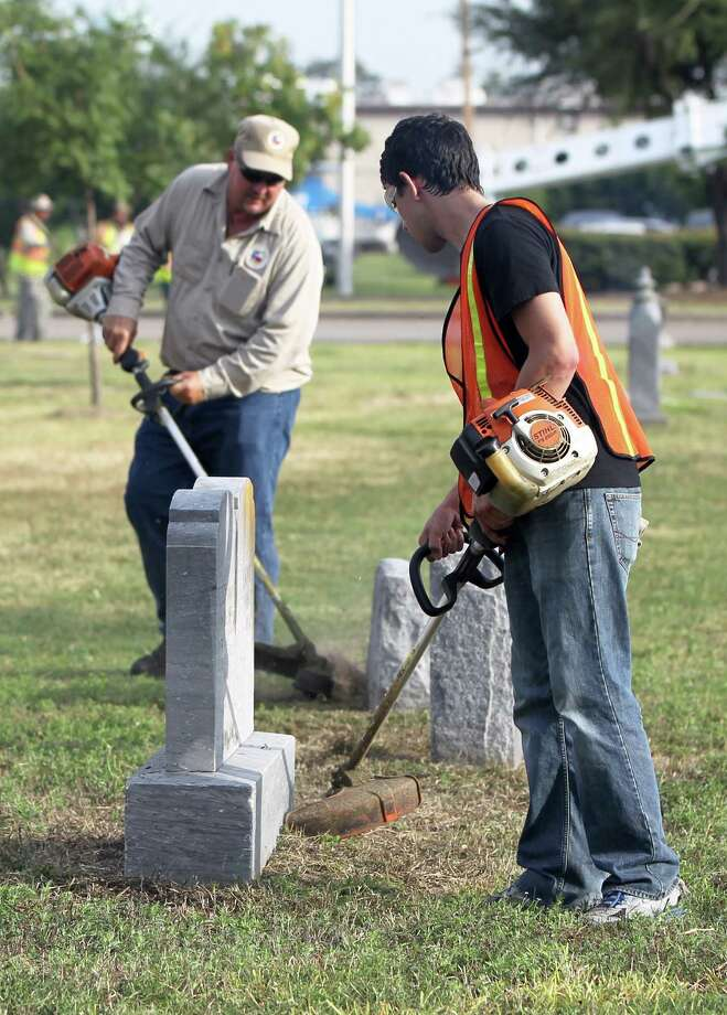 Harris County Precinct 3 caretaker Robert Kimich, left, and another worker weed eat around graves at Alief Cemetery. Photo: Karen Warren / © 2012  Houston Chronicle