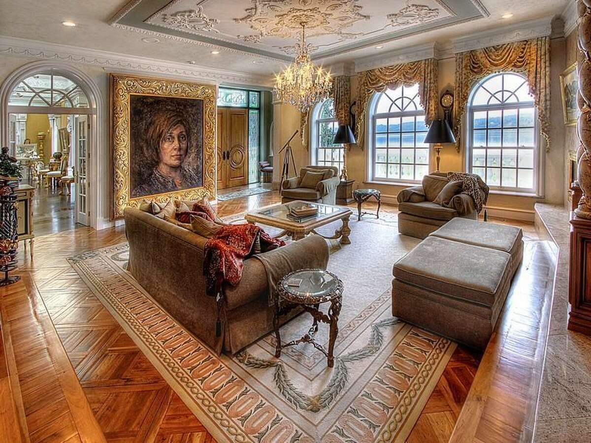 Living room of 9934 Point View St. N.E., on Johnson Point, near Olympia. The 13,335-square-foot house has four bedrooms and 5.5 bathrooms, ornate moldings, vaulted, beamed ceilings, skylights, French doors, a bar, a gym, balconies, views of Puget Sound and the Olympic Mountains, and a cannon on a 1.89-acre lot along the sound. It's listed for $6,088,800.