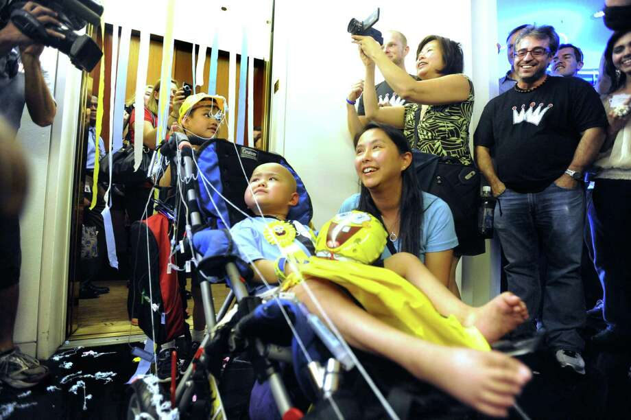 Four-year-old Alan Sanders is rolled out of an elevator with his mother, Judy Sanders, and his brother, Kevin, as his wish to press the buttons to all the floors of the tallest building in San Antonio is granted on Thursday, Sept. 27, 2012, by the Make-A-Wish Foundation. Alan, who has cancer, rode the elevator to many floors in the Weston Centre, where people that work in the building greeting him with streamers and cheers each time the doors opened. Photo: Billy Calzada, San Antonio Express-News / © 2012 San Antonio Express-News
