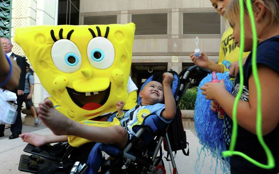 "Alan Sanders, 4, is greeted by the cartoon character ""Sponge Bob Square Pants"" and children as he arrives at the Weston Centre in downtown San Antonio to receive his wish from the Make-A-Wish program on Thursday, Sept. 27, 2012. Alan, who has cancer, wanted to ride the elevator in San Antonio's tallest building and press all the buttons to all the floors. People that work in the building greeting him with streamers and cheers each time the elevator door opened. Photo: Billy Calzada, San Antonio Express-News / © 2012 San Antonio Express-News"