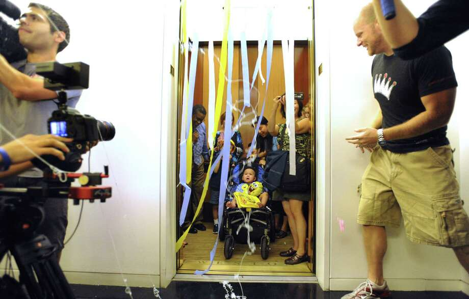 Four-year-old Alan Sanders is rolled out of an elevator as his wish to press the buttons to all the floors of the tallest building in San Antonio is granted on Thursday, Sept. 27, 2012, by the Make-A-Wish Foundation. Alan, who has cancer, rode the elevator to many floors in the Weston Centre, where people that work in the building greeting him with streamers and cheers each time the door opened. Photo: Billy Calzada, San Antonio Express-News / © 2012 San Antonio Express-News
