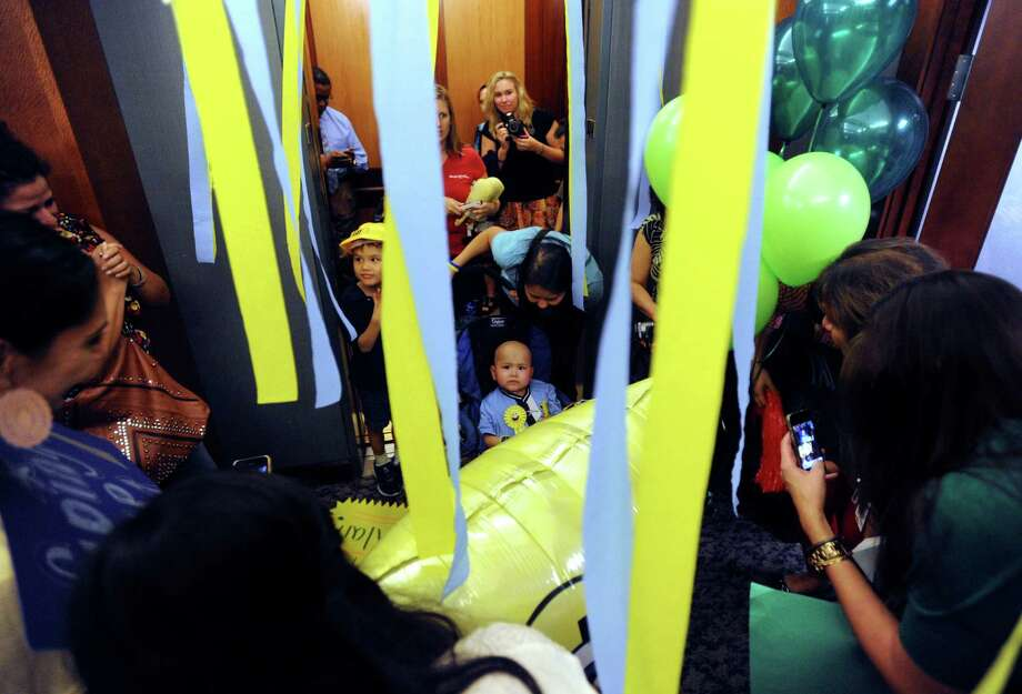 Four-year-old Alan Sanders is dwarfed by the crowd and streamers as he is rolled out of an elevator at the Weston Centre in downtown San Antonio on Thursday, Sept. 27, 2012. Alan's wish to press the buttons to all the floors of a tall building in San Antonio was granted by the Make-A-Wish Foundation, which worked with Weston Centre management. Alan, who has cancer, was festively greeted on each floor. Photo: Billy Calzada, San Antonio Express-News / © 2012 San Antonio Express-News