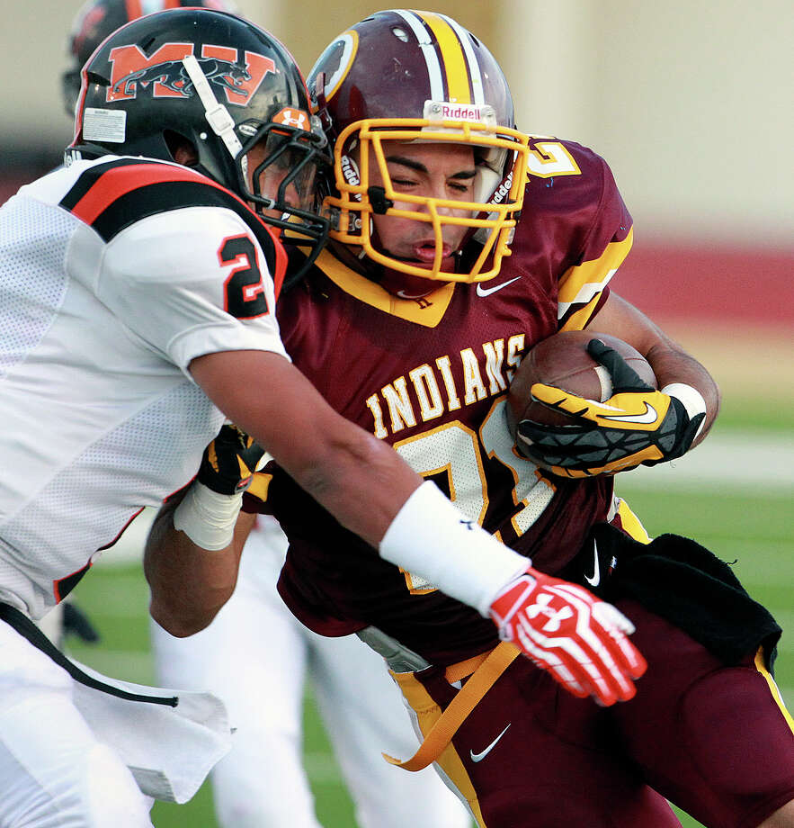 Indians running back Nicholas Martinez gets smacked by Randy Perfecto as Harlandale hosts Medina Valley at Harlandale Stadium on September 27, 2012. Photo: Tom Reel, Express-News / ©2012 San Antono Express-News