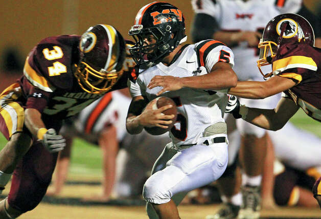 Panther running back Ben Mata gets sandwiched by tacklers as Harlandale hosts Medina Valley at Harlandale Stadium on September 27, 2012. Photo: Tom Reel, Express-News / ©2012 San Antono Express-News