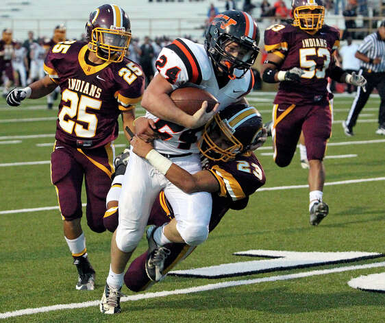 Medina Valley running back Weston Beck is hauled down at the end of a long run by Michael Ramos (23)  as Harlandale hosts Medina Valley at Harlandale Stadium on September 27, 2012. Photo: Tom Reel, Express-News / ©2012 San Antono Express-News