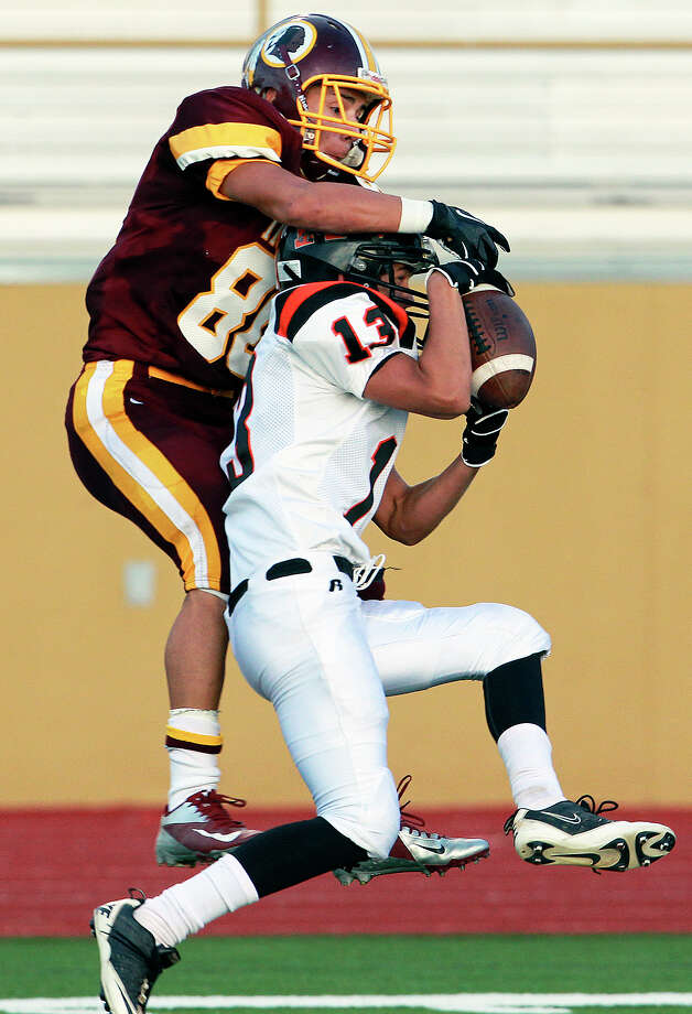 panther defender Kenny Gallegos yanks down an interception in front of Nathan Ibarra as Harlandale hosts Medina Valley at Harlandale Stadium on September 27, 2012. Photo: Tom Reel, Express-News / ©2012 San Antono Express-News