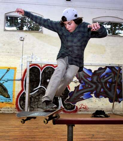 Pedro Pereira, 13, of Danbury, slides on bench, one of the tricks the skateboarders at the Harambee Center for Youth seem to favor. Photo: Carol Kaliff / The News-Times