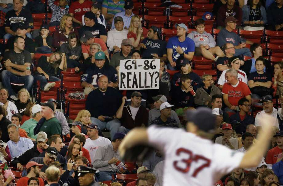 Boston Red Sox relief pitcher Mark Melancon (37) warms up in the seventh inning of a baseball game against the Tampa Bay Rays as a fan holds up a sign at Fenway Park in Boston, Wednesday, Sept. 26, 2012. The Rays won 4-2. (AP Photo/Elise Amendola) Photo: Elise Amendola, Associated Press / AP