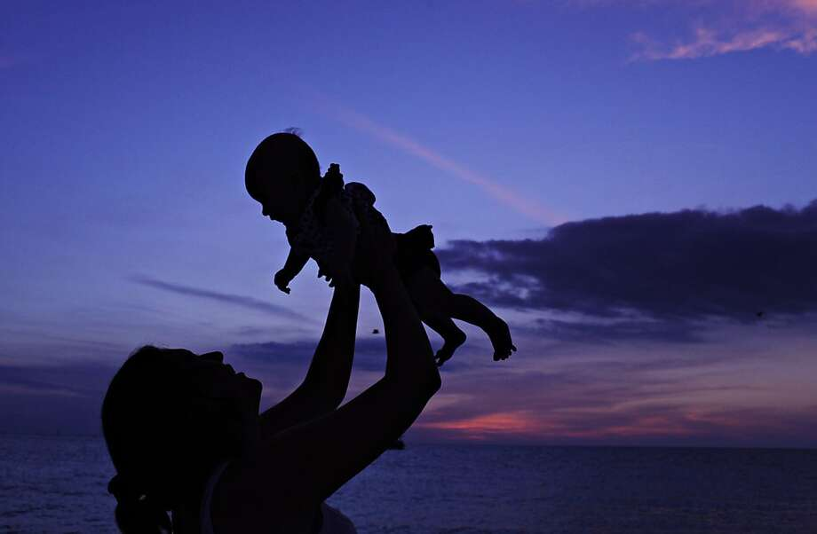 Child raising: Stella Lockhart lifts her 3-month-old daughter Baylee in the air while standing in shallow water at Madeira Beach, Fla. Photo: Melissa Lyttle, Associated Press