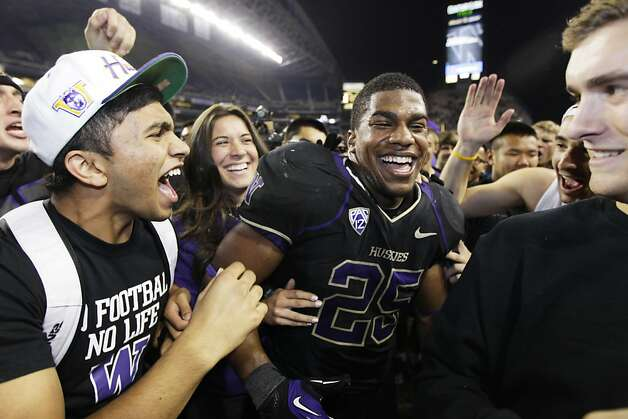 Fans surround Washington's Bishop Sankey after fans ran onto the field to celebrate Washington's 17-13 upset of Stanford in an NCAA college football game, Thursday, Sept. 27, 2012, in Seattle. (AP Photo/Ted S. Warren) Photo: Ted S. Warren, Associated Press