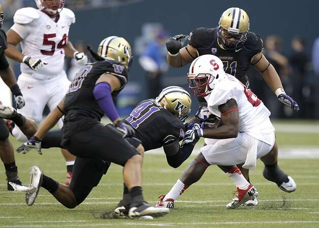 Stanford's Ty Montgomery, right, is brought down by Washington's Cason Kynes (41), as Washington's John Timu, left, and Danny Shelton, upper right, watch during the first half of an NCAA college football game, Thursday, Sept. 27, 2012, in Seattle. (AP Photo/Ted S. Warren) Photo: Ted S. Warren, Associated Press