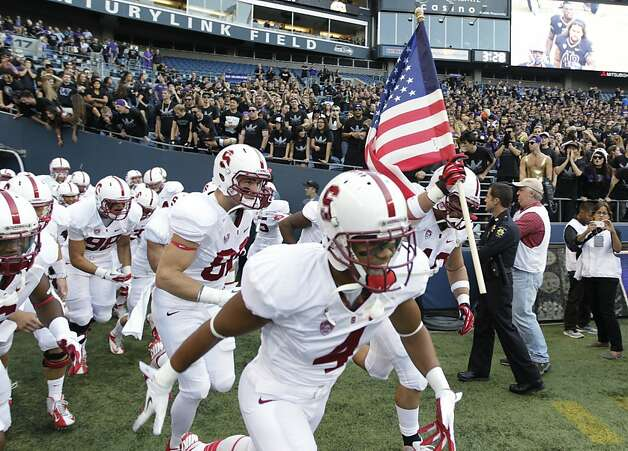 Stanford's Ben Gardner carries the U.S. flag as he leads his team onto the field for the first half of an NCAA college football game against Washington, Thursday, Sept. 27, 2012, in Seattle. (AP Photo/Ted S. Warren) Photo: Ted S. Warren, Associated Press