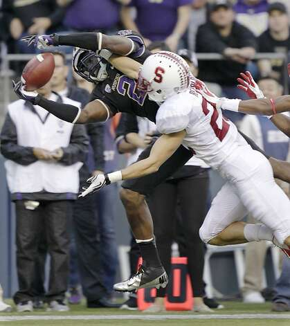 Washington's Kasen Williams (2) makes a catch ahead of the defense of Stanford's Harold Bernard, right, during the first half of an NCAA college football game, Thursday, Sept. 27, 2012, in Seattle. (AP Photo/Ted S. Warren) Photo: Ted S. Warren, Associated Press