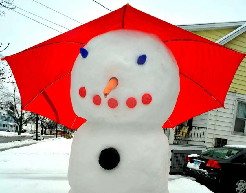 A snowman uses an umbrella to protect himself from the rain on Meadow Avenue, in Danbury, on Wendesday, Dec.9,2009.
