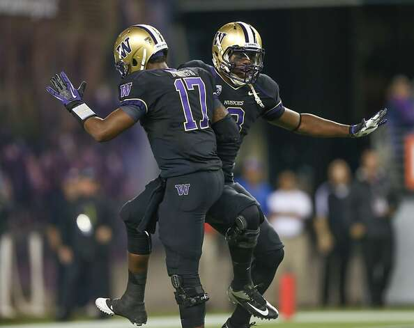 SEATTLE, WA - SEPTEMBER 27:  Quarterback Keith Price #17 of the Washington Huskies celebrates with wide receiver Kevin Smith #8 near the end of the game against the Stanford Cardinal on September 27, 2012 at CenturyLink Field in Seattle, Washington. Washington defeated Stanford 17-13.  (Photo by Otto Greule Jr/Getty Images) Photo: Otto Greule Jr, Getty Images