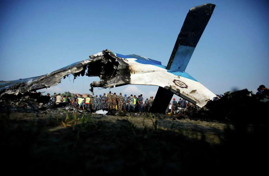 Nepalese police search through the debris at the crash site of a Sita Air airplane near Katmandu, Nepal, early Friday, Sept. 28, 2012. The plane carrying trekkers into the Everest region crashed just after takeoff Friday morning in Nepal's capital, killing all 19 people on board, authorities said. (AP Photo/Niranjan Shrestha) Photo: Niranjan Shrestha, Associated Press / AP