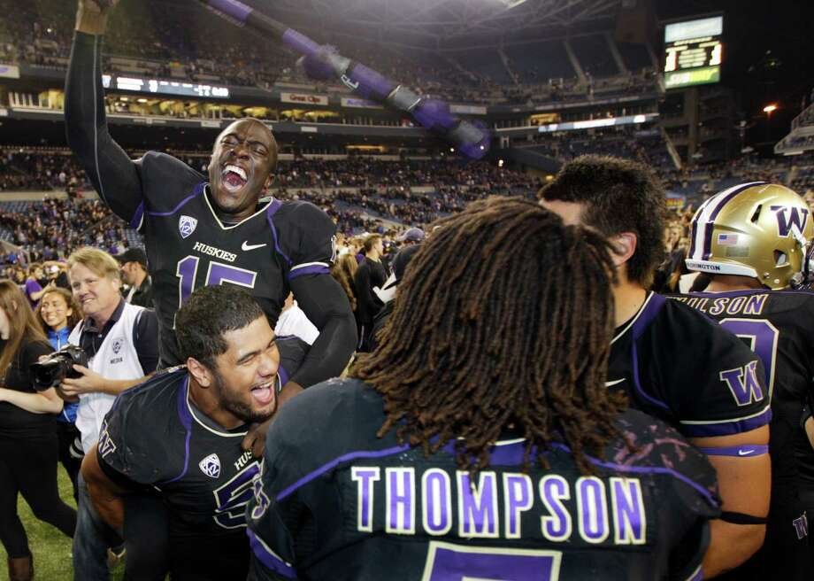 Washington's Antavius Sims, upper left, jumps on the back of teammate Sione Potoa'e, lower left, and Shaq Thompson after Washington upset Stanford 17-3, Thursday in Seattle. Photo: Ap