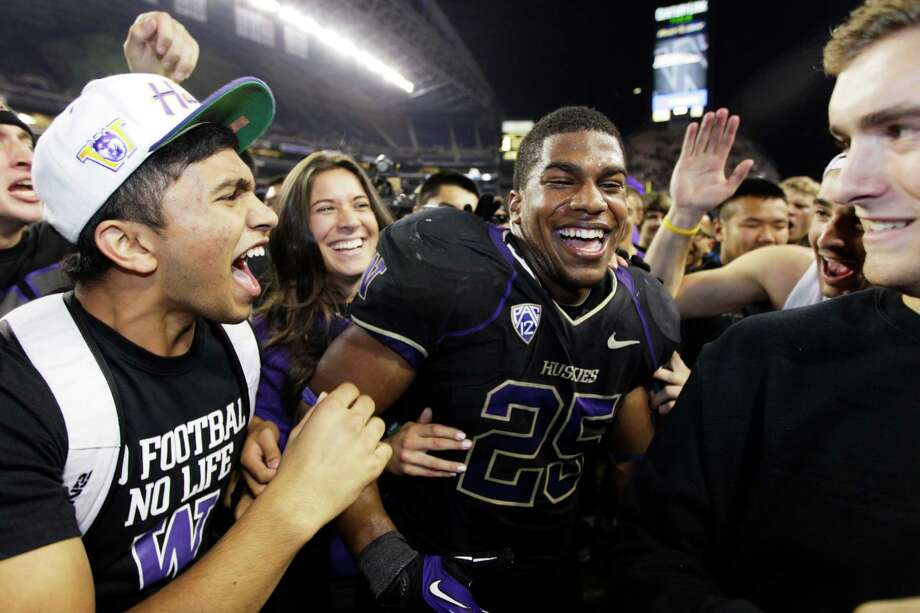 Fans surround Washington's Bishop Sankey after fans ran onto the field to celebrate Washington's 17-13 upset of Stanford Thursday in Seattle. Photo: Ap