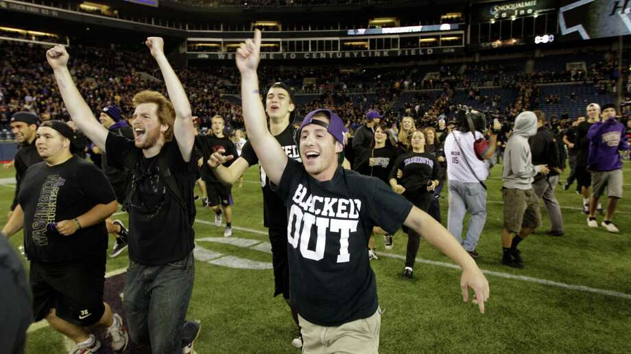 Washington football fans run onto the field after Washington upset Stanford, 17-13. Photo: Ap