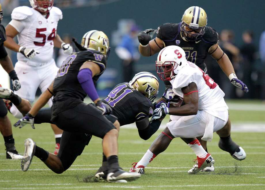 Stanford's Ty Montgomery, right, is brought down by Washington's Cason Kynes (41), as Washington's John Timu, left, and Danny Shelton, upper right, watch. (AP Photo/Ted S. Warren) Photo: Associated Press