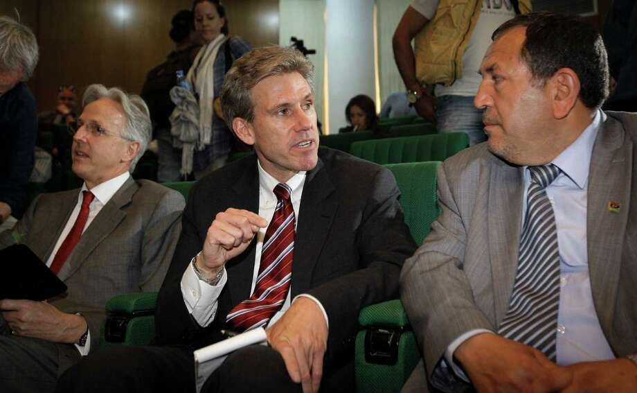 In this photo taken Monday, April 11, 2011, then U.S. envoy Chris Stevens, center, accompanied by British envoy Christopher Prentice, left, speaks to Council member for Misrata Dr. Suleiman Fortia, right, at the Tibesty Hotel where an African Union delegation was meeting with opposition leaders in Benghazi, Libya. Libyan officials say the U.S. ambassador and three other Americans have been killed in an attack on the U.S. consulate in the eastern city of Benghazi by protesters angry over a film that ridiculed Islam's Prophet Muhammad. (AP Photo/Ben Curtis) Photo: Ben Curtis, Associated Press / AP