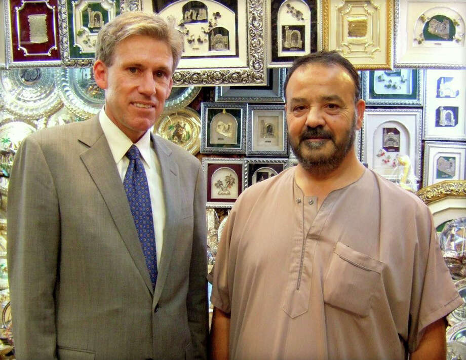 In this photo posted on the U.S. Embassy Tripoli Facebook page on Aug. 12, 2012, U.S. Ambassador to Libya Christopher Stevens, left, poses with a shop owner in Tripoli, Libya. Libyan officials say the U.S. ambassador and three other Americans have been killed in an attack on the U.S. consulate in the eastern city of Benghazi by protesters angry over a film that ridiculed Islam's Prophet Muhammad. (AP Photo/U. S. Embassy Tripoli) Photo: Anonymous, Associated Press / US Embassy Tripoli