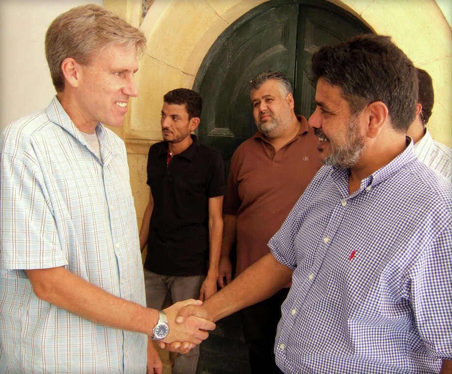 In this photo posted on the U.S. Embassy Tripoli Facebook page on Aug. 27, 2012, U.S. Ambassador to Libya Christopher Stevens, left, shakes hands with a Libyan man in Tripoli, Libya. Libyan officials say the U.S. ambassador and three other Americans have been killed in an attack on the U.S. consulate in the eastern city of Benghazi by protesters angry over a film that ridiculed Islam's Prophet Muhammad. (AP Photo/U. S. Embassy Tripoli) Photo: Anonymous, Associated Press / US Embassy Tripoli