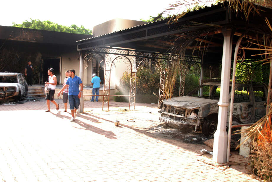 Libyans walk on the grounds of the gutted U.S. consulate in Benghazi, Libya, after an attack that killed four Americans, including Ambassador Chris Stevens, Wednesday, Sept. 12, 2012. The American ambassador to Libya and three other Americans were killed when a mob of protesters and gunmen overwhelmed the U.S. Consulate in Benghazi, setting fire to it in outrage over a film that ridicules Islam's Prophet Muhammad. Ambassador Chris Stevens, 52, died as he and a group of embassy employees went to the consulate to try to evacuate staff as a crowd of hundreds attacked the consulate Tuesday evening, many of them firing machine-guns and rocket-propelled grenades. Photo: Ibrahim Alaguri, Associated Press / AP