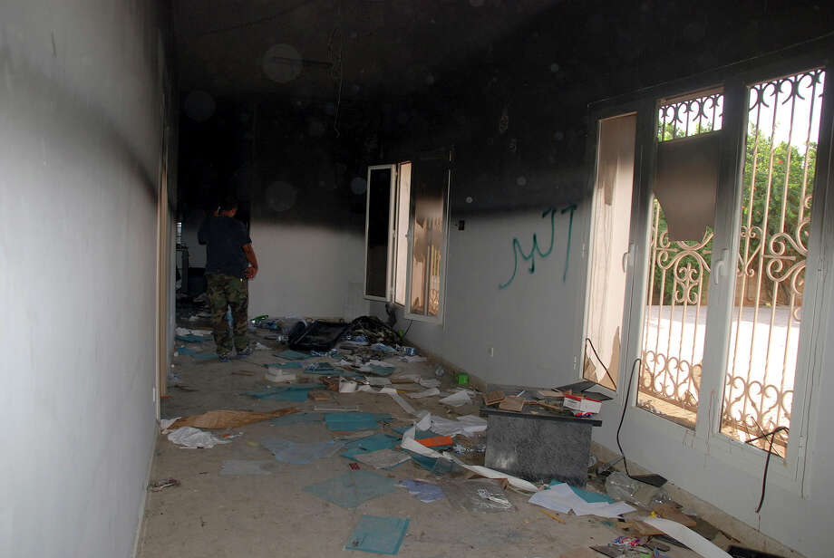 A man walks through a room in the gutted U.S. consulate in Benghazi, Libya, after an attack that killed four Americans, including Ambassador Chris Stevens, Wednesday, Sept. 12, 2012. The American ambassador to Libya and three other Americans were killed when a mob of protesters and gunmen overwhelmed the U.S. Consulate in Benghazi, setting fire to it in outrage over a film that ridicules Islam's Prophet Muhammad. Ambassador Chris Stevens, 52, died as he and a group of embassy employees went to the consulate to try to evacuate staff as a crowd of hundreds attacked the consulate Tuesday evening, many of them firing machine-guns and rocket-propelled grenades. Partial graffiti reads, akbar, Arabic for great. Photo: Ibrahim Alaguri, Associated Press / AP