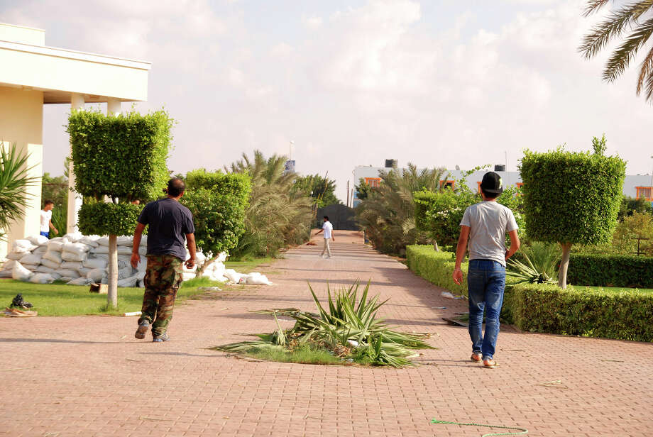 Libyans walk on the grounds of the U.S. consulate in Benghazi, Libya, after an attack that killed four Americans, including Ambassador Chris Stevens, Wednesday, Sept. 12, 2012. The American ambassador to Libya and three other Americans were killed when a mob of protesters and gunmen overwhelmed the U.S. Consulate in Benghazi, setting fire to it in outrage over a film that ridicules Islam's Prophet Muhammad. Ambassador Chris Stevens, 52, died as he and a group of embassy employees went to the consulate to try to evacuate staff as a crowd of hundreds attacked the consulate Tuesday evening, many of them firing machine-guns and rocket-propelled grenades. Photo: Ibrahim Alaguri, Associated Press / AP