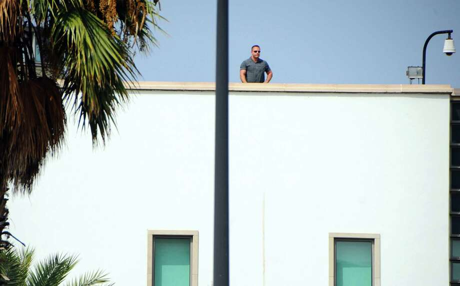 A man stands atop the United States embassy in Tunis, Wednesday, Sept.12, 2012 as ultraconservative Muslims demonstrate outside the embassy to demand the closure of the embassy and the departure of the ambassador. The American embassies in Algeria and Tunisia warned of more protests Wednesday, following attacks by protesters in neighboring Libya in which the U.S. ambassador and three embassy staff were killed. Photo: Hassene Dridi, Associated Press / AP