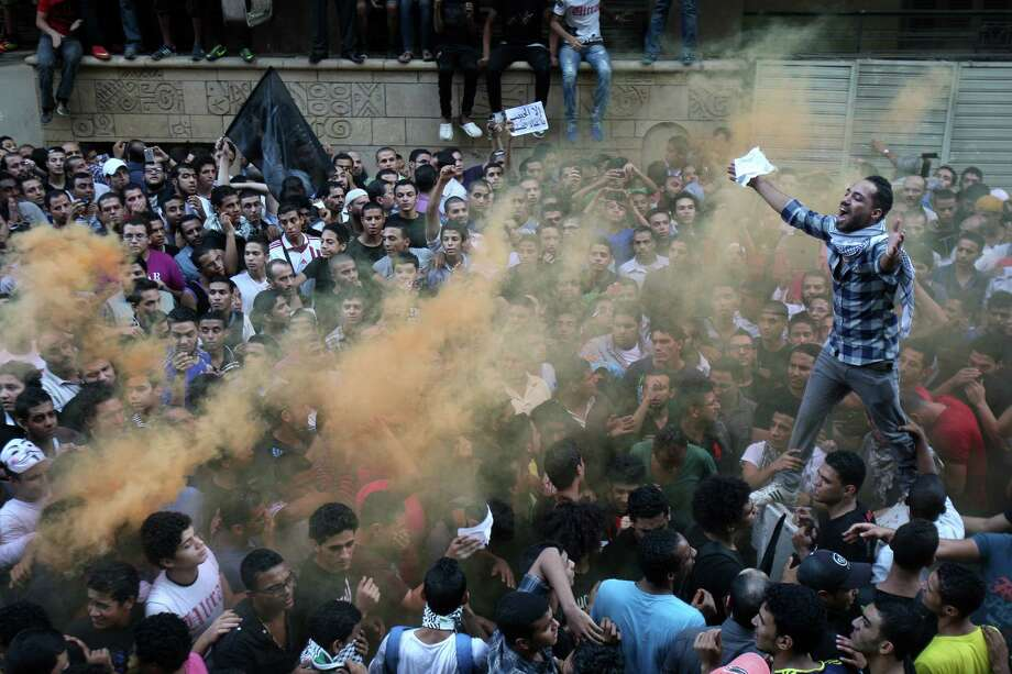 Protesters chant slogans amid orange smoke outside the U.S. embassy in Cairo, Egypt, Tuesday, Sept. 11, 2012. Egyptian protesters, largely ultra conservative Islamists, have climbed the walls of the U.S. embassy in Cairo, went into the courtyard and brought down the flag, replacing it with a black flag with Islamic inscription, in protest of a film deemed offensive of Islam. Photo: Mohammed Abu Zaid, Associated Press / AP