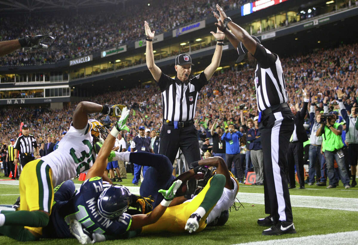 Side Judge Lance Easley, center, looks at back judge Derrick Rhone-Dunn as Easley calls a Seattle Seahawks touchdown catch by Golden Tate and Rhone-Dunn says the catch is no good in the final second of the Seattle Seahawks and Green Bay Packers game Monday Night Football game on September 24, 2012 at CenturyLink FIeld in Seattle. The controversial call put the Seahawks over the Packers to win 14 to 12.