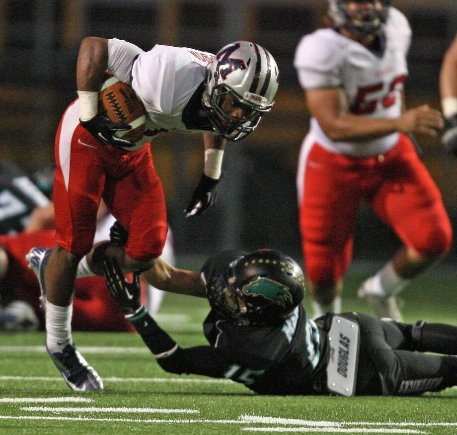 Manvel wide receiver Carlos Thompson (left) escapes the tackle of Pasadena Memorial's Thomas Gamez during the first half of a high school football game, Thursday, September 27, 2012 at Veterans Memorial Stadium in Pasadena, TX. Photo: Eric Christian Smith, For The Chronicle