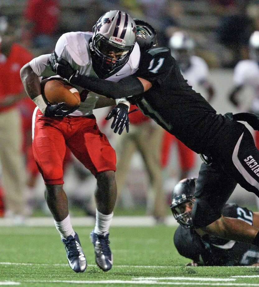 Manvel wide receiver Carlos Thompson (left) is tackled by Pasadena Memorial defensive back Aaron Robinson during the first half of a high school football game, Thursday, September 27, 2012 at Veterans Memorial Stadium in Pasadena, TX. Photo: Eric Christian Smith, For The Chronicle