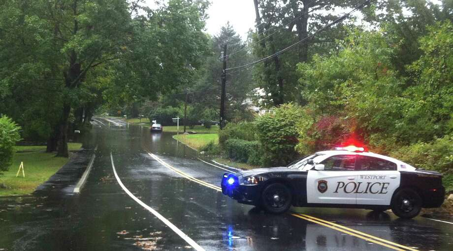 A police cruiser blocks access to a stretch of Imperial Avenue that was under water from the downpours at midday Friday. Photo: Paul Schott / Westport News