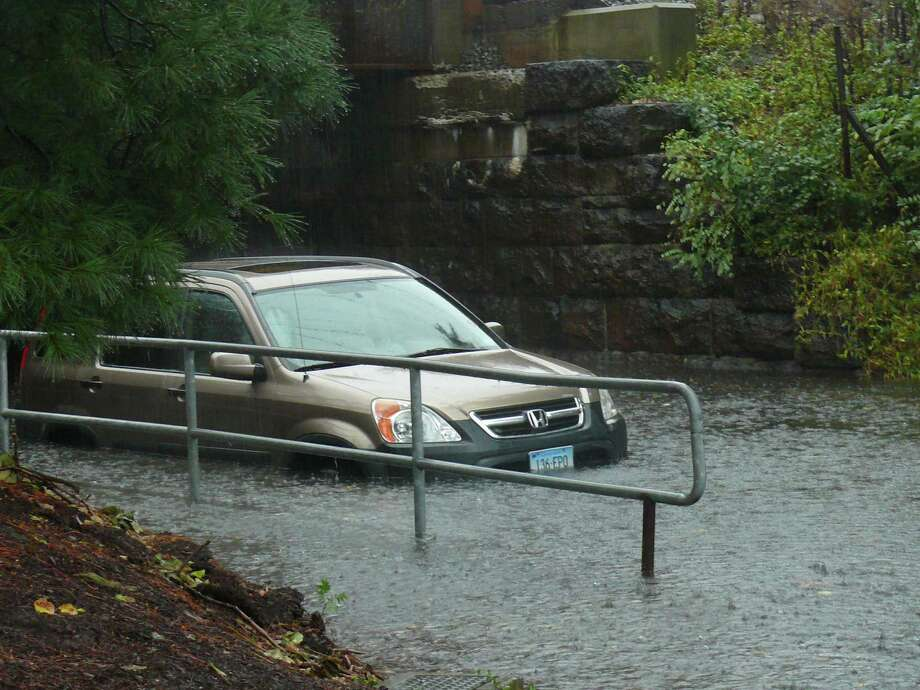 A car is stuck under the viaduct at Post and Round Hill roads Friday morning. Photo: Genevieve Reilly / Fairfield Citizen