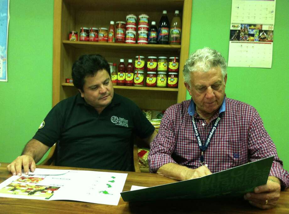 Julio Castillo, the president of Danbury-based MegaBusiness Corp., shares a prospectus with Tony Rizzo Sr., co-founder of the Rizzo Companies and Castillo's landlord. Castillo's import-export business on Lee Mac Avenue features food from Latin America. Photo: Brian Koonz