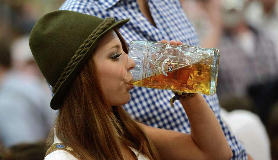 "A young woman wearing traditional Bavarian dress ""Dirndl"" enjoys a beer under a tent during the Oktoberfest beer festival fair at the Theresienwiese in Munich, southern Germany, on Sept. 27, 2012. The world's biggest beer festival Oktoberfest will run until Oct. 7, 2012. AFP PHOTO / CHRISTOF STACHE Photo: CHRISTOF STACHE, Getty / 2012 AFP"