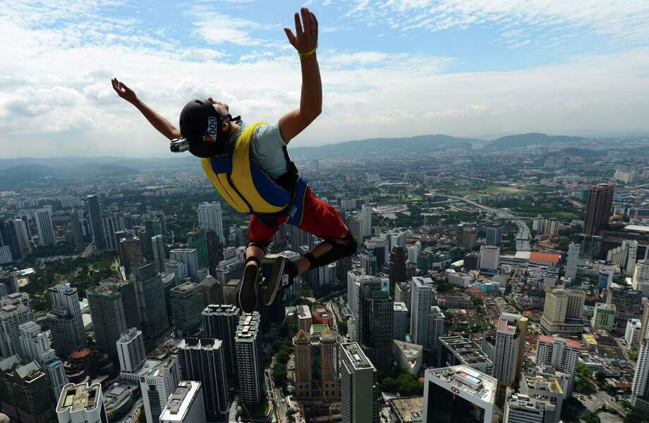 Base jumper Anton Chervyakov from Russia leaps from the top of the 421-meter Kuala Lumpur Tower during the International Tower Jump in Kuala Lumpur on Sept. 27, 2012.  Some 95 professional basejumpers from 18 countries are taking part in the annual event.      AFP PHOTO / MOHD RASFAN Photo: AFP, Getty / 2012 AFP