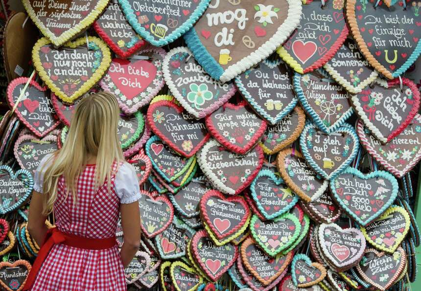A woman stands in front of gingerbread hearts at the Theresienwiese Oktoberfest fair grounds in Muni