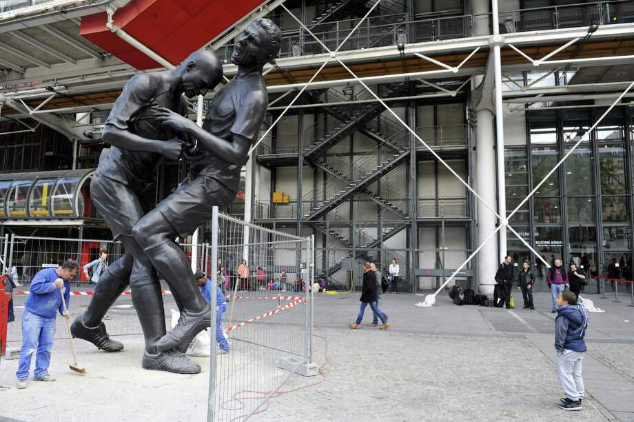 "Employees sweep on Sept. 26, 2012, in Paris near a bronze sculpture by Algerian artist Adel Abdessemed displayed in front of the Centre Pompidou contemporary art center. The sculpture immortalizes the ""headbutt"" given by the French former football champion Zinedine Zidane to Italian player Materazzi during the World Cup final in 2006. The Centre Pompidou will dedicate a retrospective to Abdessemed from Oct. 3, 2012, to Jan. 7, 2013.    AFP PHOTO MEHDI FEDOUACH Photo: MEHDI FEDOUACH, Getty / 2012 AFP"