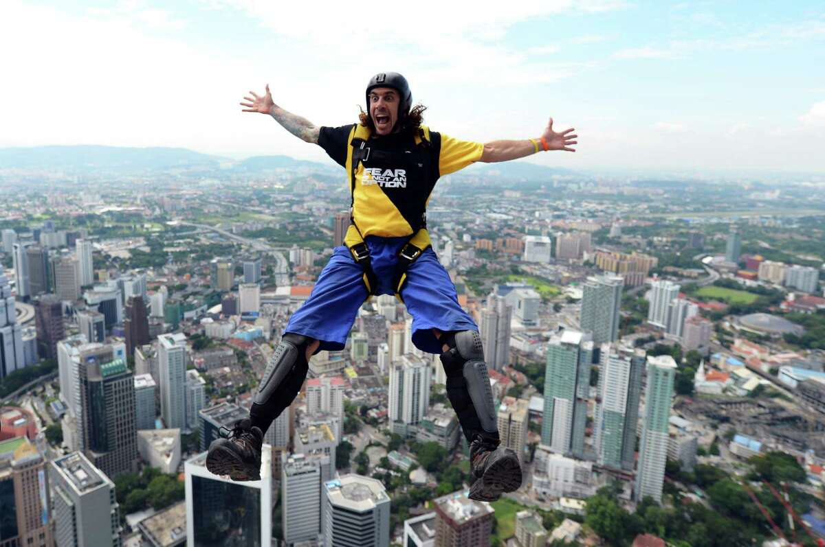 Base jumper Chris McDougall from Australia leaps from the top of the 421-meter Kuala Lumpur Tower during the International Tower Jump in Kuala Lumpur on Sept. 27, 2012. Some 95 professional basejumpers from 18 countries are taking part in the annual event. AFP PHOTO / MOHD RASFAN